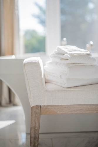 Folded White Bath Towels Placed on Upholstered Bathroom Furniture - Bathroom Decor Vaughan by Royal Interior Design Ltd