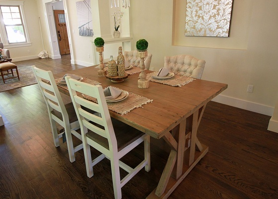 Brown Wooden Dining Table With Four Padded Chairs Inside Room with Beige Painted Walls