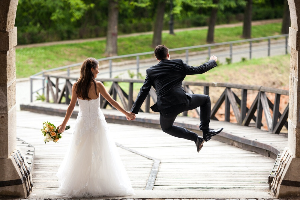 groom+jumping+in+air+holding+bride's+hand.jpg