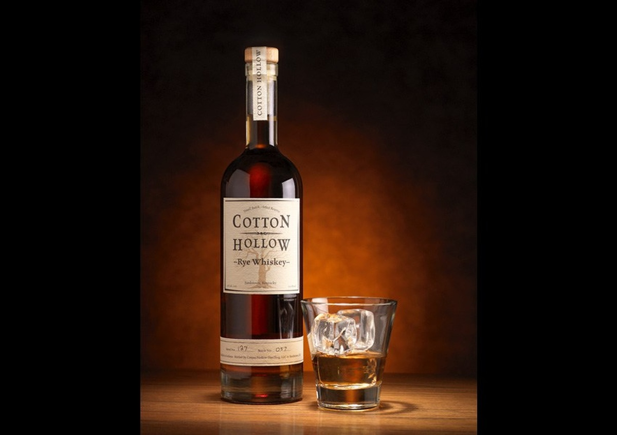 Cotton Hollow Rye Whiskey bottle and a shot glass with ice cubes - Joe Robbins Photography
