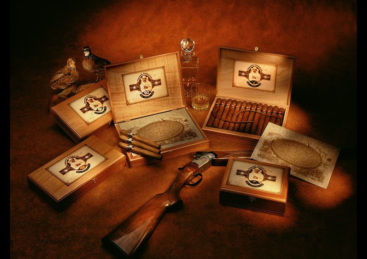 Boxes containing cigars with a shotgun next to them