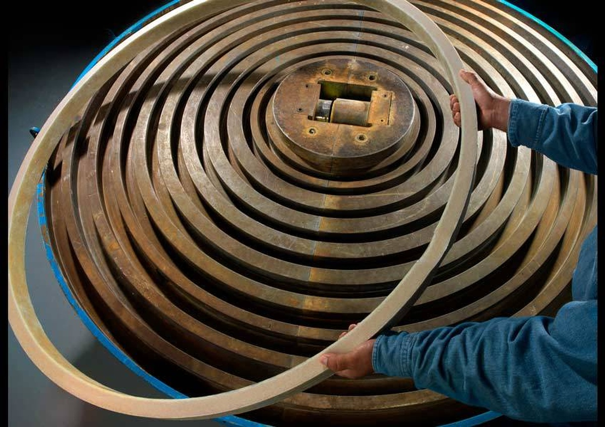 A worker arranging huge metal rings inside a factory
