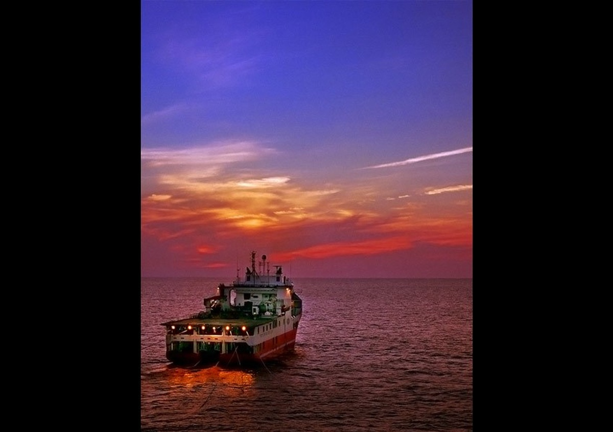 A boat sailing towards the sunset captured beautifully by Joe Robbins