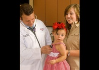 A doctor examining a child while her mother looks on -  Professional Photography in Texas by Joe Robbins