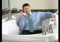 Man in a Bathtub holding shower head - Joe Robbins Photography