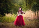 Girl playing violin in field captured by Natalie Edmundson Photography