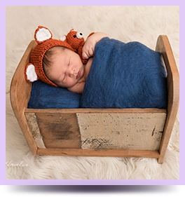 Baby sleeping in cradle captured by Natalie Edmundson - Newborn Photographer Grovetown