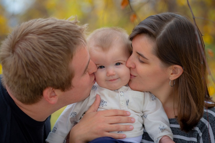 Parents Kissing Baby captured by Family Photographer Minneapolis at Mode T Productions