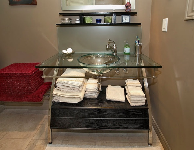 Modern Glass Bathroom Sink with towels placed on wood vanity