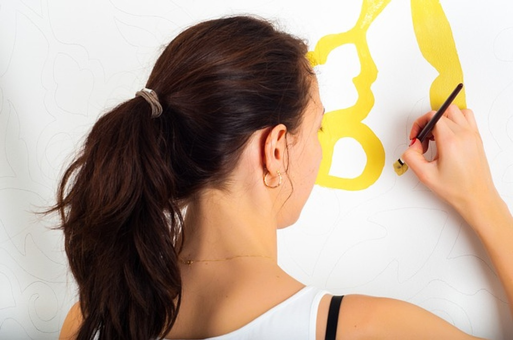 A woman painting on a wall, one of kid-friendly renovation ideas